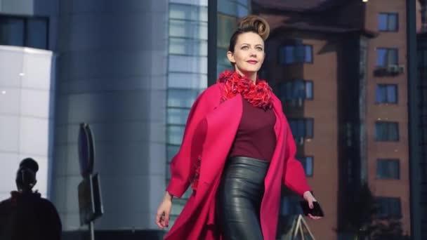 sebevědomá žena s krásnou neobvyklé kadeřní chodí přes město na jaře. Dívka na pozadí moderní architektury. Zpomalený pohyb