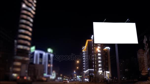 záběry z času zanikla městské scény s osvětlené prázdný billboard na straně ulice s auty v pohybu