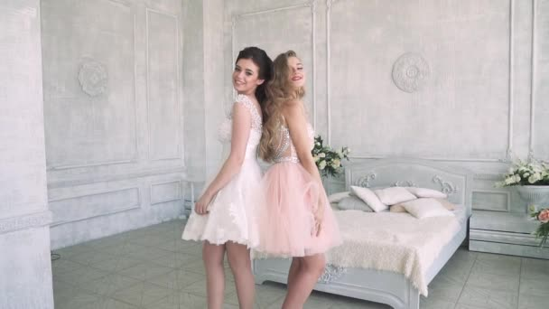 Girls in cocktail dresses posing on camera