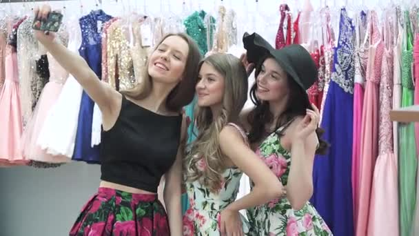Three beautiful girlfriends are photographed and fooled around in the store