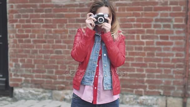 attraktives junges Mädchen macht Fotos mit einer Filmkamera