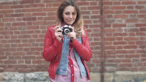 Portrét mladé okouzlující ženy s kamerou retro Foto film v rukou