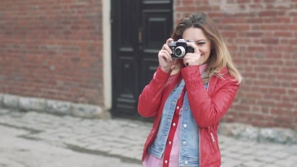 Mädchen fotografiert ihre Freunde mit einer Filmkamera. Blondine im roten Sakko macht Fotos und lächelt