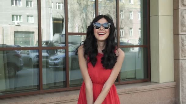 Beautiful girl in red dress and wearing sunglasses posing and smiling at camera on urban architecture background.