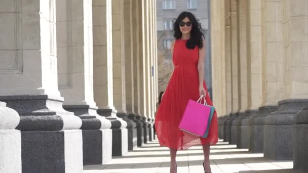 Charming girl with shopping bags in hands.. The brunette is happy with successful shopping, she smiles and rejoices. Charming girl with shopping bags in hands. Professional model posing on camera.