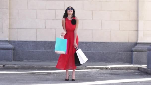 Charming young girl posing on camera with shopping bags. The brunette in sunglasses is happy with successful shopping, she smiles and rejoices. SLOW MOTION