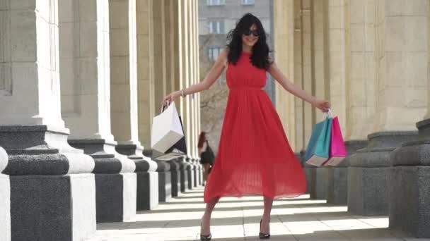 Hezká žena v červených šatech drží nákupní tašky. Krásná mladá dívka v sluneční brýle v létě. Zpomalený pohyb