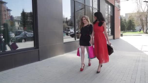 b3ae935868 dos mejores amigos ir de compras. Rubia y morena caminando por la calle con  bolsas de ...