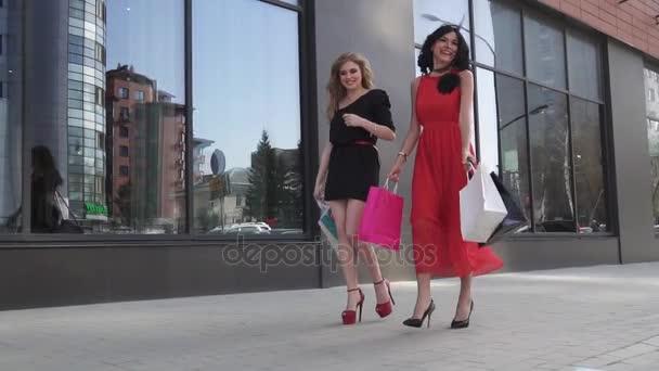 Krásné mladé dívky přiblížit windows obchod. Nejlepší přátelé trávit čas společně. Blondýna a bruneta procházel městem letní s nákupní tašky. Zpomalený pohyb