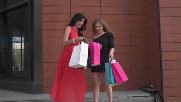 přátel předvést sebe nakupování. Krásné dívky zájem o akvizice se zájmem. Blondýna a bruneta procházel městem letní s nákupní tašky. Zpomalený pohyb