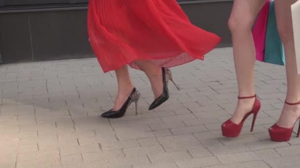 gambe sexy di una bella ragazze che va con borse della spesa. rallentatore