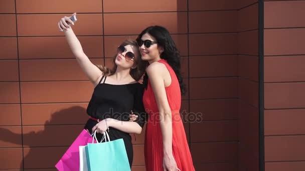Nejlepší přátelé uživatele udělat selfie po nakupování. krásné dívky v sluneční brýle s nákupní tašky v ruce fotí a usmívá se. Zpomalený pohyb