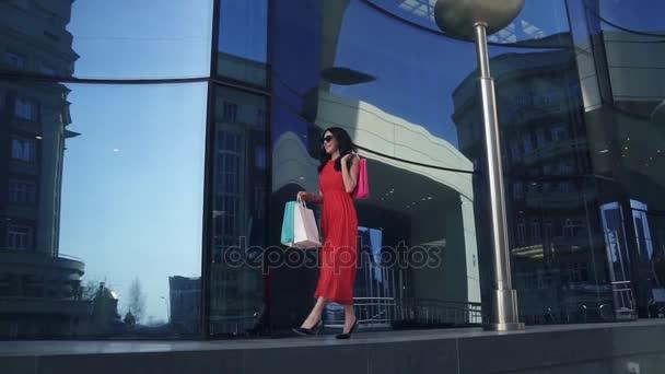 okouzlující mladá dívka v červených šatech se baví s nákupní tašky v ruce. bruneta, procházky v létě city. Zpomalený pohyb