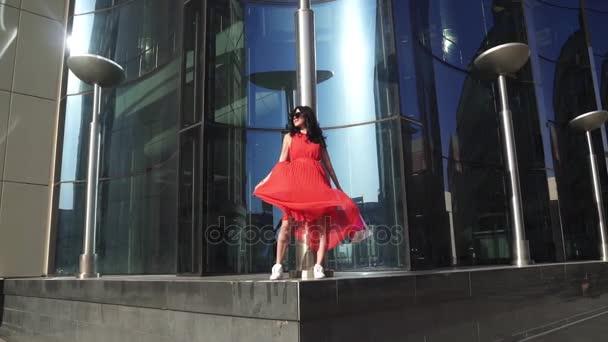 Portrét mladé sexy dívka s sexy nohy v červených šatech. Bruneta v sluneční brýle po nakupování Zpomalený pohyb