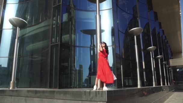 Krásná dívka v červených šatech na budování pozadí s modrými brýlemi. Bruneta v sluneční brýle se usmívá na kameru. Zpomalený pohyb