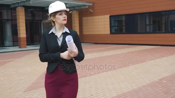 architect young woman walking by a construction site and holding blueprints. Builder in hard hat. businesswoman at work