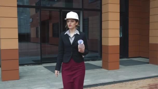Mladá žena architekt v stavbařskou přílbu s plány v rukou. Tvůrce v přilbu. podnikatelka v práci
