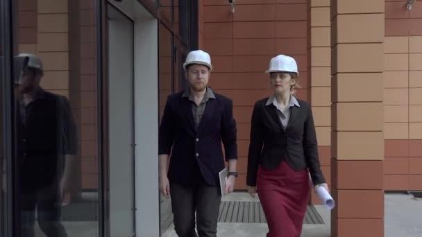 architekti, kontrola staveniště. mladá žena a její kolegyně jsou na pozadí moderní budovy. inženýr pracuje v přilbách. Zpomalený pohyb