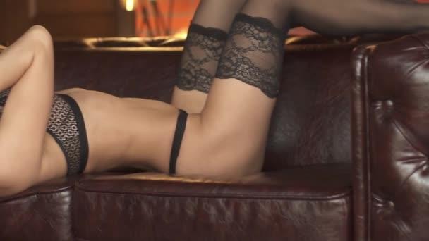 sexy model se pohybuje krásně, ležící na couchr kůže. Sexy dívka ve spodním prádle tancuje erotický tanec. Closeup nahá dívka. Zpomalený pohyb