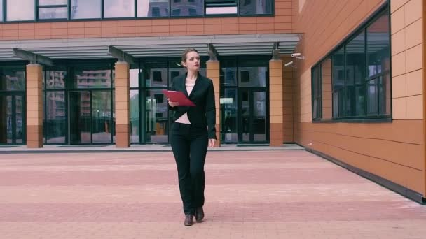 Beautiful confident young business is in a hurry to negotiate. Girl in business clothes with a red folder in hands on the background of an office building. SLOW MOTION