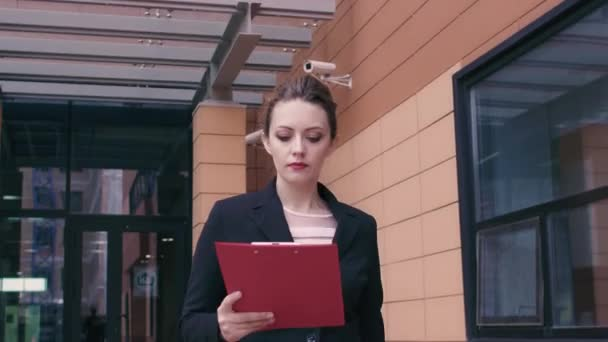 businesswoman reading documents on the go. girl in a hurry for a business meeting