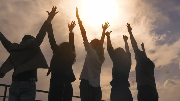 silhouette of people rejoicing and lifting up his hands. a group of successful businessmen happy and celebrate the victory on the roof of the business center. slow motion
