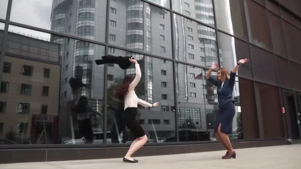 dvě dívky v oblečení podnikání je šťastný, skákání a baví. obchodní žena slaví úspěch a vítězství. podnikatelé na pozadí budovy ze skla. Zpomalený pohyb