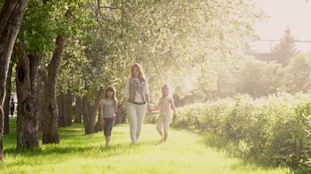 Mother walks with her daughters along the avenue of apple trees. The little girl is holding her mother by the hand. Childs and parent in a summer park at sunset.