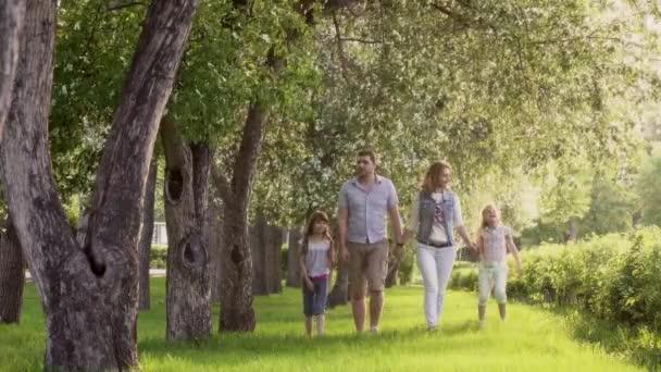 šťastná rodina v letním parku nedaleko rozkvetlé jabloně. otec, matka a dvě dcery trávit čas spolu venku při západu slunce.