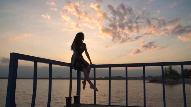 Krásná dívka sedí na molu u západu slunce a swingu ty nohy. Silueta krásné dívky v lehké šaty při západu slunce