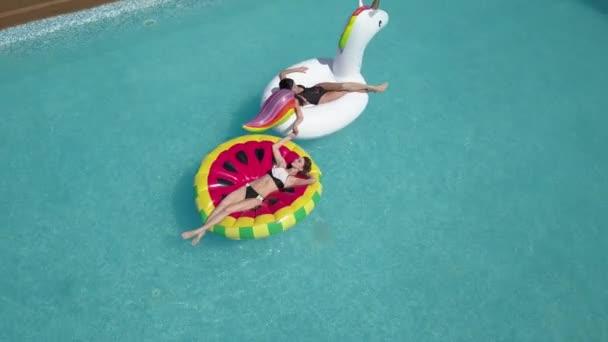 Anténa - mladé sexy ženách, které 20s pokládání a uvolněný poblíž bazén na letní dovolenou. Přítelkyně jsou opalovací ležící na nafukovací matrace v podobě jednorožec a meloun