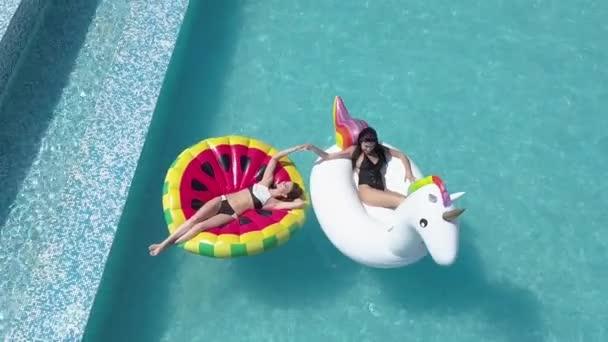 Légi - gondtalan lányok pihenhetnek és napozhatnak, feküdt egy matrac a medencében. Miután a forró hétvégi barátnője. Quadrocopter felvételkészítés