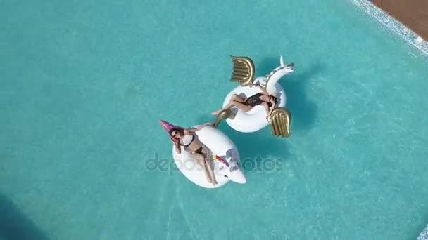 Antenna - fiatal nők, napozás-on air matracok az egyszarvú és a Pegasus. Vonzó fiatal lányok többi napos medencével. Quadrocopter felvételkészítés