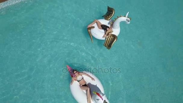 Anténa - krásné dívky v bikinách na nafukovací matraci pegasus a jednorožec v bazénu. Mladá žena se těší slunné odpoledne s koktejlem v ruce. Střelba s quadrocopter