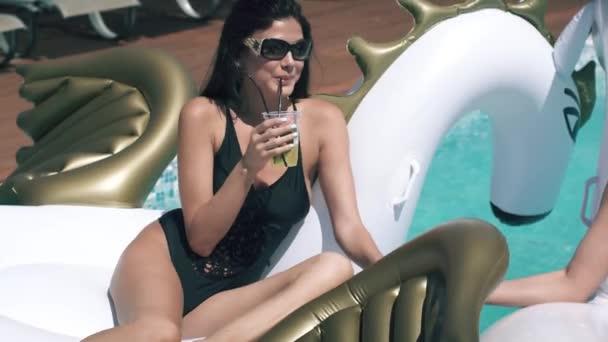dívky jsou pití osvěžující koktejly na pláži. Kamarádky opalovat se a plavat na nafukovací matrace ve venkovním bazénu