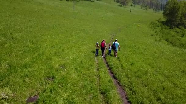 Antény. Rodinné cestující s malými dětmi. otec, matka a dcera šla na výlet. turisté s batohy, na louce