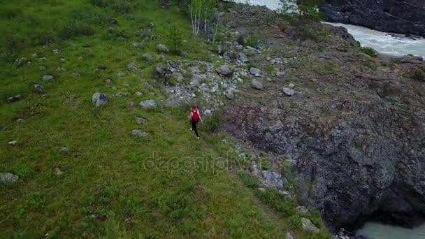 Antény. dívka cestovatel s batohem chodí podél útesu v horách. žena turistické byl na výletě. Altaj, Sibiř. Letecká kamera natáčela