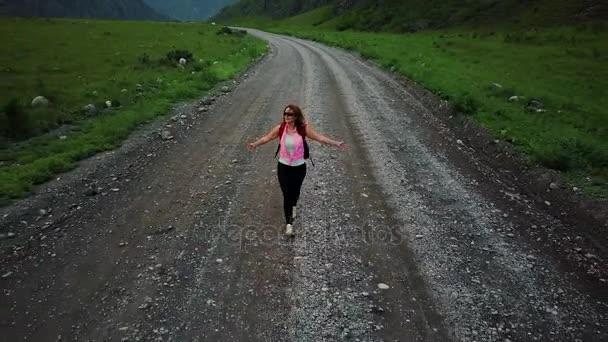 Antény. žena turistické jde na prašné cestě. pohled ze vzduchu. dívka cestovatel s batohem. krásná střela z Kvadrokoptéra. Kontrolo, prostor, příroda. Altaj, Sibiř. Letecká kamera natáčela