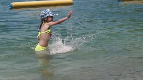 kleines Mädchen im Wasser zu spielen. Baby Spaß und planschen im Wasser. Slow-motion