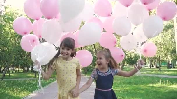 dvě holčičky radostně běh přes léto Park s bublinami v jeho rukou. Sestřičky, drželi se za ruce a usmívá se. Zpomalený pohyb