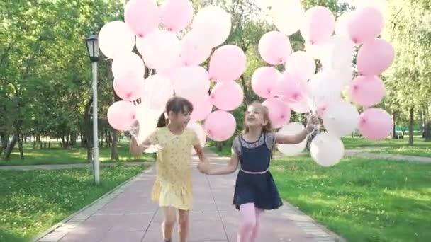Bezstarostné děti jsou spokojený s balónky, které jejich rodiče jim dal. Holčičky si teplý slunečný letní den. Zpomalený pohyb