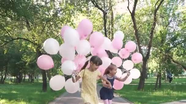 egy boldog gondtalan gyermekkor. két kis barátnője kezét, és fut át a nyári Park gazdaság színes léggömbök. lassú mozgás