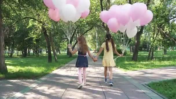 děti projít letní Park s balonky. dvě malé holčičky se drží hodně barevné balónky. pohled zezadu