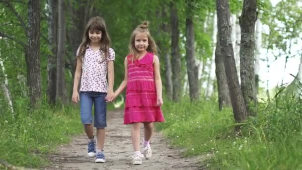 two little girls hold hands and walk down the green alley. children walk outdoors. two little sisters. slow motion