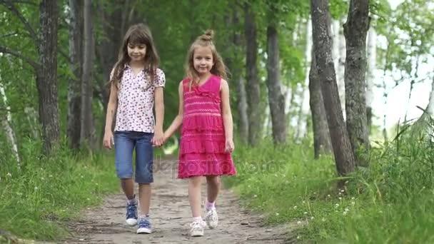 Zwei kleine Mädchen halten sich an den Händen und gehen die grüne Gasse hinunter. Kinder gehen ins Freie. zwei kleine Schwestern. Zeitlupe