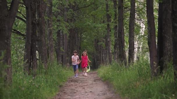 két kislány fut le a zöld sikátorban, és kéz a kézben. meg költeni idő kint. gyerekek természet. lassú mozgás