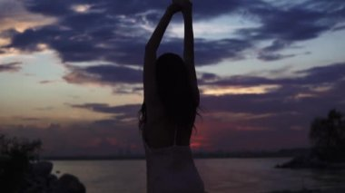 Silhouette of dancing girl at sunset on the seashore. slow motion