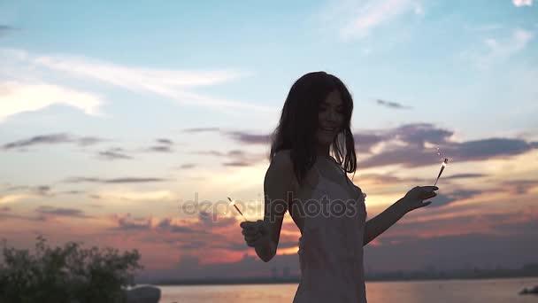 tanzt das Mädchen fröhlich bei Sonnenuntergang. junge Frau im Cocktailkleid mit bengalischen Lichtern. Zeitlupe