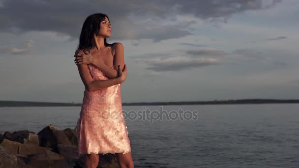 Sinnliche Portrait eines Mädchens gegen den Himmel und das Meer. Süße junge Mädchen in Cocktail-Kleid bewundert den Sonnenuntergang