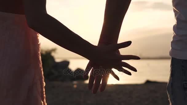 Férfi és női kézi zár-megjelöl ellen a lenyugvó nap. Gyengéd érintés a két szerelmes. Szerelem, romantika, barátság